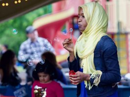 A girl blows bubbles at the 2019 World Refugee Celebration in downtown Fort Wayne.