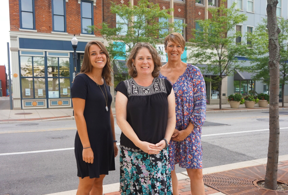 Aubrie Tinsley (left), Sara Gensic (center), and Suzy Ulmer (right) in downtown Fort Wayne with the Alyssum Montessori School behind them on the left.
