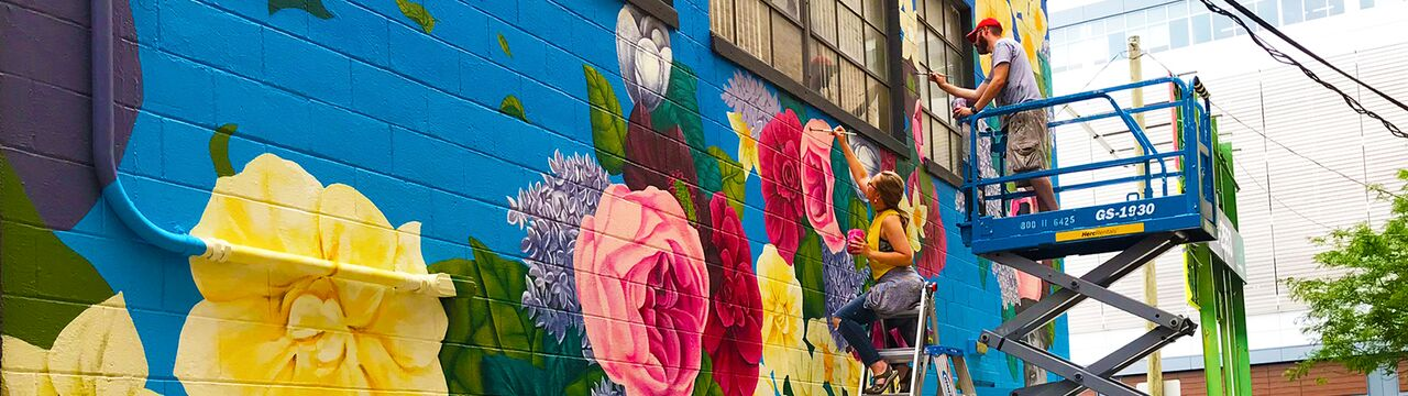 Artist Tim Parsley and students from the University of Saint Francis paint a mural in the alley between Wayne Street and Berry Street as part of Art This Way. <span class='image-credits'>By Stephen J. Bailey</span>