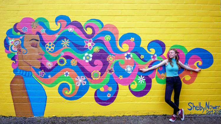 Art student Shelby Nower, 21, stands in front of her mural in downtown Decatur.