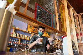 Barista Caleb North serves a hot pumpkin spice chai with almond milk at Firefly Coffee House.