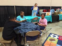Attendees make fleece blankets together at last year's Holiday Giveback.