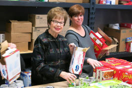 Volunteers Janet Finkel and Bonnie Pomerantz sort donations.