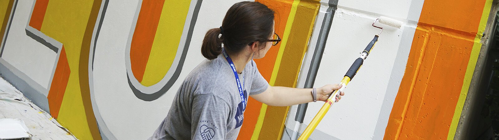 Community volunteers help artist Shawn Dunwoody paint a mural in a downtown Fort Wayne alleyway.