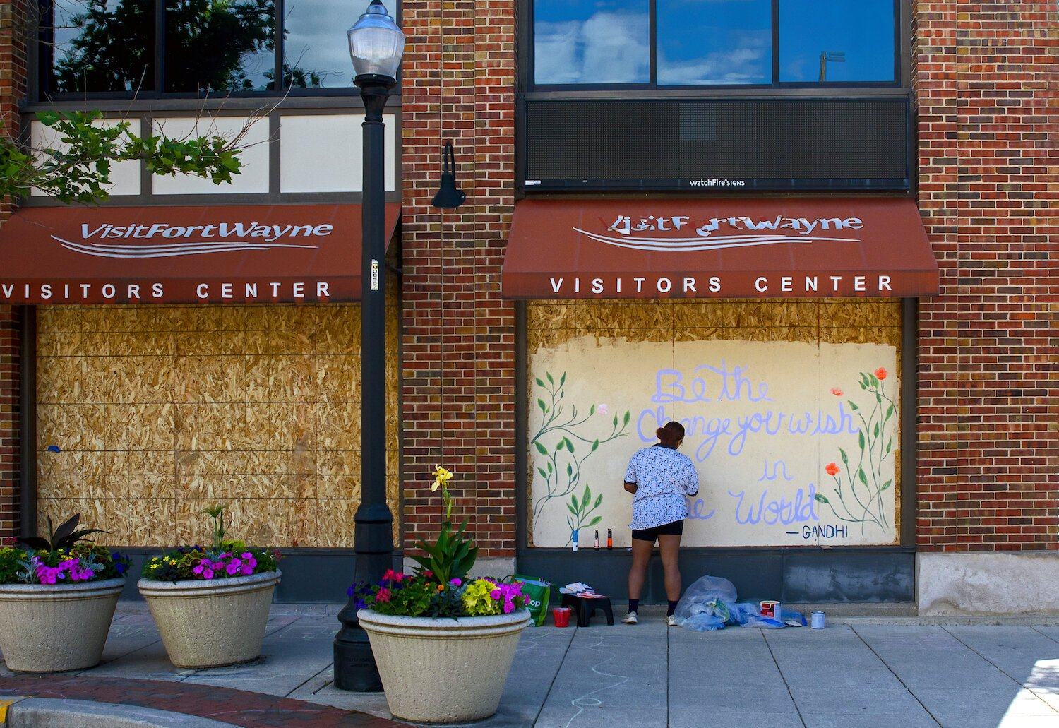 Isis Shaw paints a mural on Visit Fort Wayne's windows in downtown Fort Wayne.
