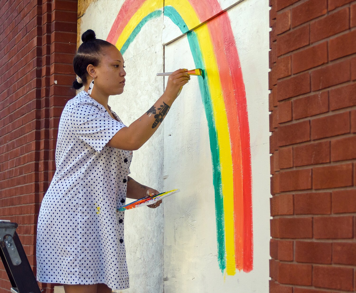 Jasmine Christensen paints a rainbow mural in downtown Fort Wayne.