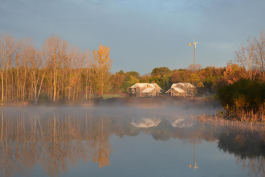 Merry Lea's Rieth Village is reflected in the Kesling Wetland, a nine-acre wetland restoration.