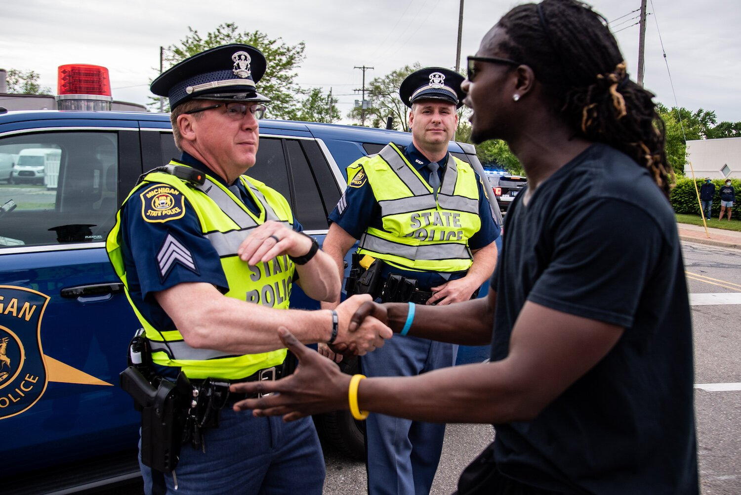 Trokon Jayqua, right, thanks police officers during a march to protest the death of George Floyd and social injustice June 1 on Mission Street in Mount Pleasant, MI.