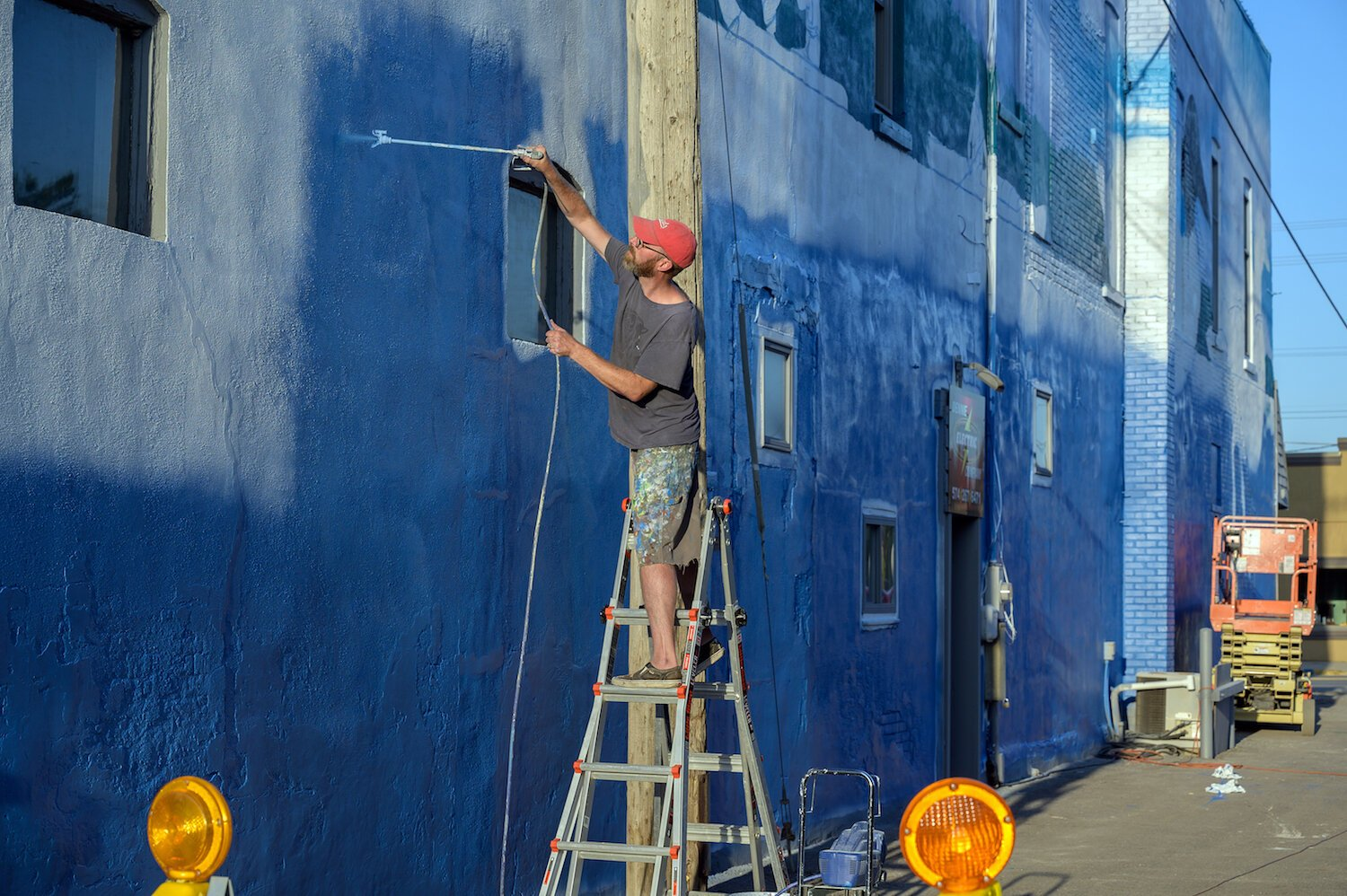 Tim Parsley works on a mural in downtown Warsaw.