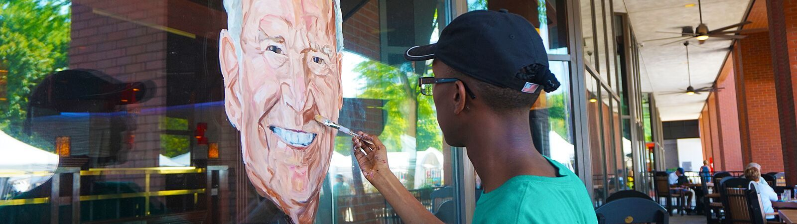 An artist paints a mural of Fort Wayne Mayor Tom Henry during the Three Rivers Festival downtown. <span class='image-credits'>By Stephen J. Bailey</span>