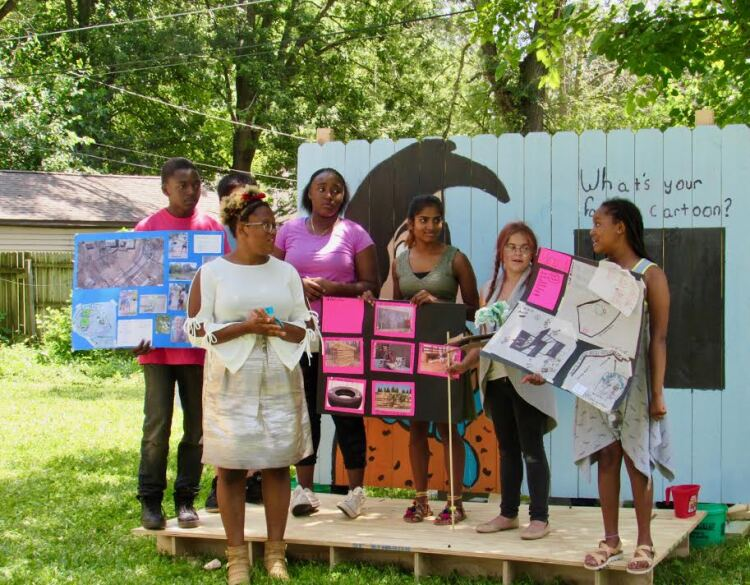 A Tired-a-Lot Summer Studio group presents their designs for a community space in front of a mural they designed and painted.