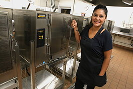 Ruiz poses with her favorite kitchen tool: The industrial steamers at the Community Harvest Food Bank's shared kitchen.